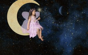 A little girl dressed like a fairy sitting on a crescent moon with a starry background