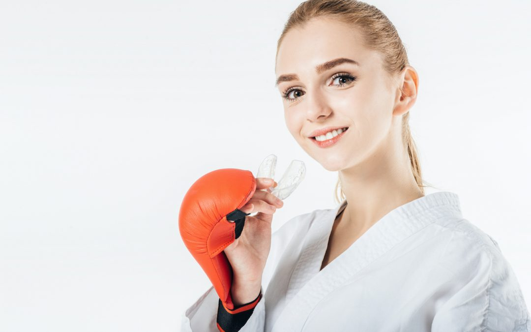 Athletic boxing female with a mouthguard on white background