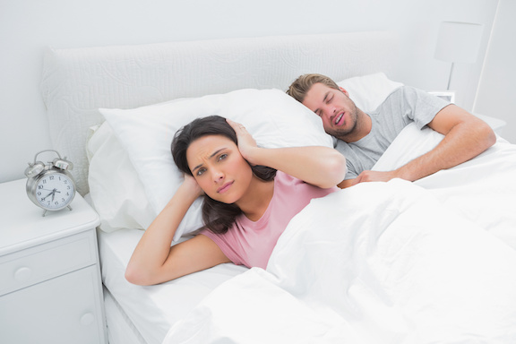 Snoring man is annoying his wife who tries to sleep in her bed