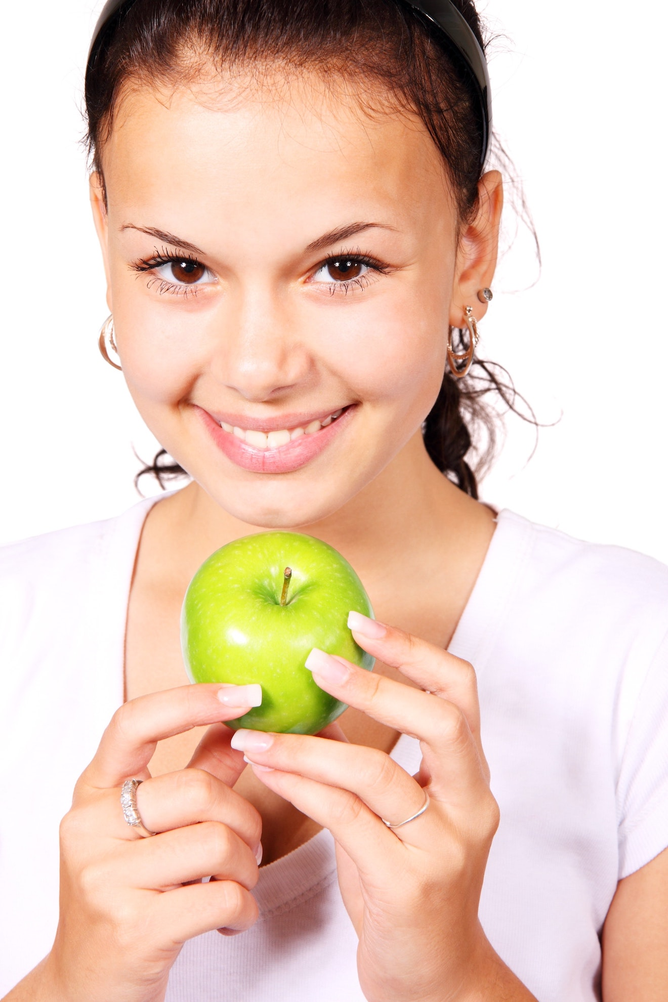 a women holding a green apple and smiling